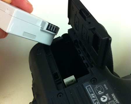 Canon Rebel LP-E8 battery being inserted into camera